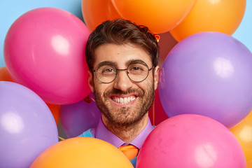 Birthday and celebration concept. Close up portrait of smiling man with bristle, wears spectacles for good vision, looks through colorful balloons, has party mood, makes photos before guests come