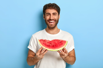 Waist up shot of smiling man enjoys summer day, holds slice of fresh ripe watermelon, wants to eat...
