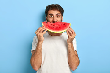 Funny man holds half of red watermelon near face, has glad surprised look, dressed casually, has...