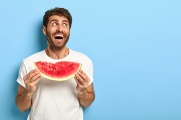 Chilling glad male bought watermelon at fruit market, holds slice, has good appetite, wears casual white t shirt, looks aside, laughs happily, isolated on blue background with space area for advert