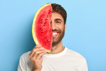Taste of summer concept. Cheerful young man covers half of face with big slice of watermelon, has oraganic healthy nutrition, dressed casually, poses on blue background, enriches with vitamins.