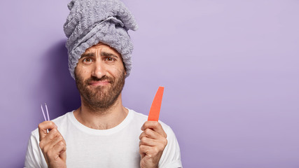 Image of dissatisfied male puzzled as doesnt know what to do with beauty tools, holds tweezers and nail file, wears wrapped towel on head, smircs face, has manicure, removes hair on eyebrows