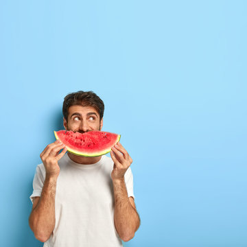 Vertical shot of attractive young man covers mouth with slice of red juicy watermelon, enjoys eating seasonal tropical fruit during summer period, wears white t shirt, poses indoor. What nice taste!