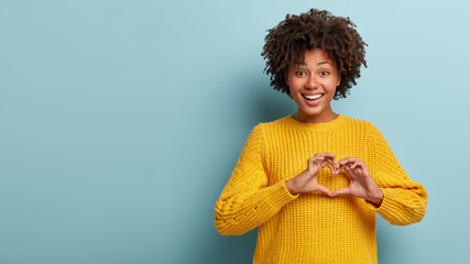 Pleasant looking smiling woman with Afro hairstyle makes heart gesture, confesses boyfriend in hearwarming feelings, shows love sign, wears oversized yellow jumper. Spread only love and care
