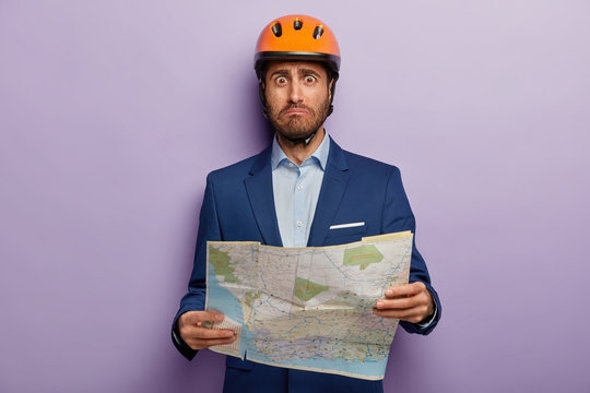 Photo of embarrassed male architect learns location for building, holds paper map, wears headgear, formal suit, looks in dissatisfaction, isolated on purple background. People, emotions, destination