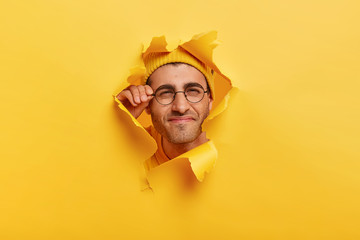 Male face in paper torn hole. Man looks curiously, has happy gaze, touches frame of glasses, poses over yellow background, makes funny photos, tries to see something in distance, has bad vision