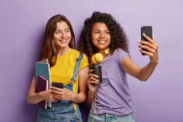 Joyful millennial companions have charming smiles, take selfie on cell phone, pose with takeout coffee and textbooks, wear casual outfit, isolated on purple background. Lets make awesome pics together