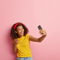Smiling African American woman has video conversation with friend, looks hapily at smartphone camera, points with index finger, dressed casually, models over pink wall blank copy space above