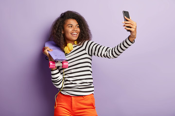 Stylish smiling millennial female holds skateboard, makes selfie, enjoys spare time, stands indoor against purple background, uses mobile phone. People, ethnicity, hobby and entertainment concept