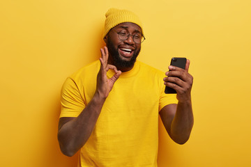 Satisfied dark skinned man makes video call via cell phone, makes okay gesture, confirms everything...