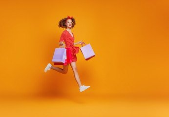 concept of shopping purchases and sales of happy   girl with packages  on yellow background.
