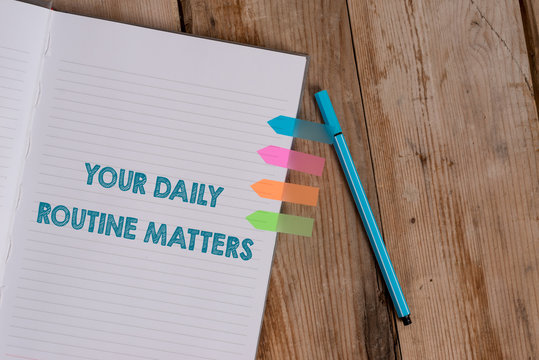 Conceptual hand writing showing Your Daily Routine Matters. Concept meaning practice of regularly doing things in fixed order Striped notebook colored arrow banners ballpoint wooden background