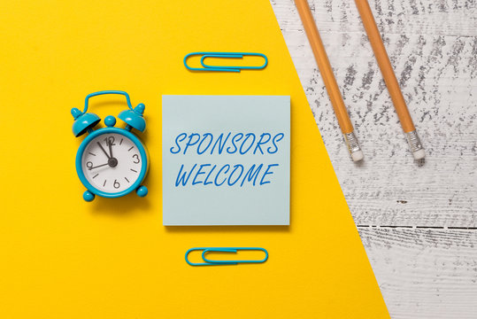 Text sign showing Sponsors Welcome. Business photo text announcing that you accept investing in your company Notepad clips colored paper sheet markers alarm clock wooden background