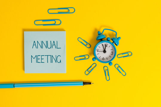 Word writing text Annual Meeting. Business photo showcasing yearly meeting of the general membership of an organization Metal alarm clock wakeup clips ballpoint notepad colored background