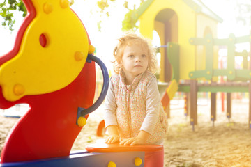 red-haired little girl plays in a childrens park on the playground and  camera lens catches  picks up the orange sunset lights from the sun