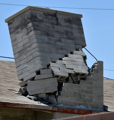 A damaged chimney remains on a roof after an earthquake near Trona