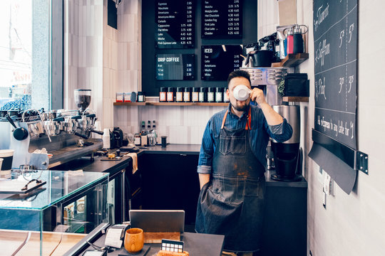 Caucasian young man barista drinking coffee from white cup during his lunch break at work place. Funny authentic real life moment of small business owner employee staff.