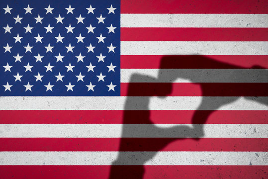 Hands making heart shape shadow on American flag background on textured grunge concrete wall