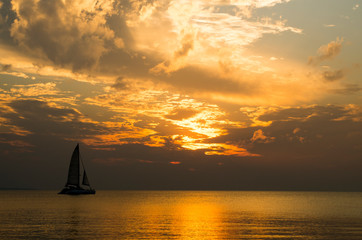 Sailing boat (sailboat, yacht) during the beautiful, orange and cloudy sunset