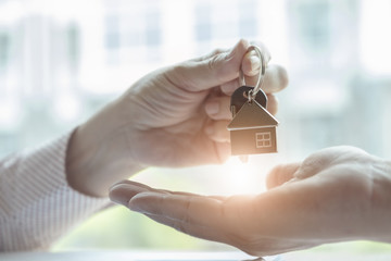 Real estate agents agree to buy a home and give keys to clients at their agency's offices. agreement and contract concept.