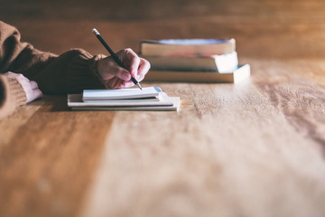 Closeup image of a woman writing on blank notebook on wooden table