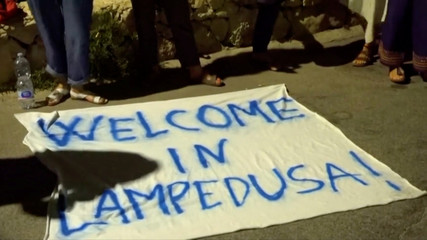 "People stand near a banner reading ""Welcome in Lampedusa"" as migrants disembark a rescue boat in the port of Lampedusa"