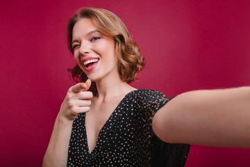 Sensual girl with cute tattoo on arm making selfie in studio. Short-haired curly woman in black dress taking picture of herself in room with purple interior.