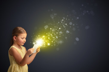 Little cute girl playing on sparkling tablet