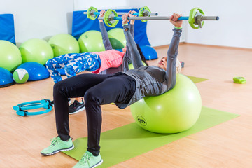 Two slim women exercising with barbell and Swiss ball in front of the mirror in training hall