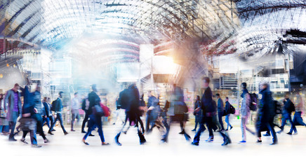 Beautiful motion blur of walking people in train station. Early morning rush hours, busy modern life concept. Ideal for websites and magazines layouts