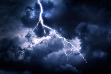 Lightning strike on a cloudy dark rainy sky.