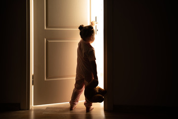 Little girl opens the door to the light in darkness Wall mural