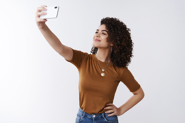 Sharing positive emotions internet audience. Attractive cheerful stylish lifestyle female blogger extend arm holding smartphone taking selfie make happy smile face look screen phone camera