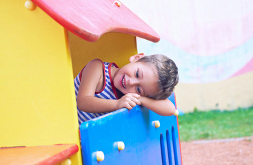 Funny cute happy little boy playing on the playground. The emotion of happiness, fun and joy.