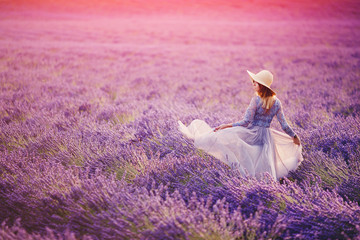Woman in lavender flowers field at sunset in purple dress. France, Provence