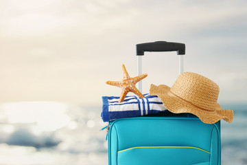 Wall Mural - holidays. travel concept. blue suitcase with female hat, starfish and beach towel in front of tropical background