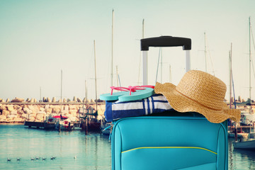 Wall Mural - holidays. travel concept. blue suitcase with female hat, flip flips and beach towel in front of marina with yachts background