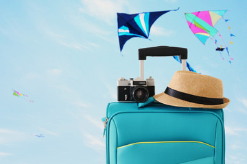 Wall Mural - recreation image of traveler luggage, camera and fedora hat infront of blue sty with flying colorful kites background. holiday and vacation concept