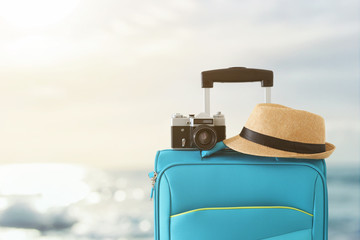 Wall Mural - recreation image of traveler luggage, camera and fedora hat infront of tropical sunset background. holiday and vacation concept
