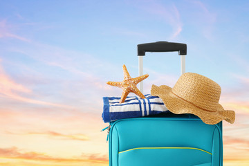 Wall Mural - holidays. travel concept. blue suitcase with female hat, starfish and beach towel in front of tropical sunset sky background