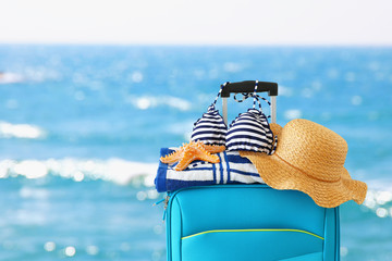 Wall Mural - holidays. travel concept. blue suitcase with female hat, starfish, bikini and beach towel in front of tropical background