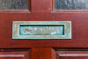 Old retro mailbox on the wooden doors. Hole on the wooden doors for mail.