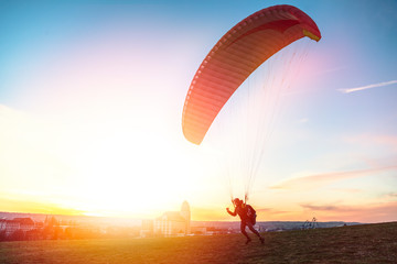 Paraglider getoff ground with wind against sunset