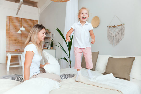 Happy mother and her daughter child girl playing and hugging in bedroom.