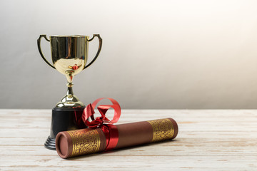 Golden trophy and graduation scroll on white table.Education concept.