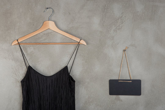 Fashion and shopping concept - blank blackboard and beautiful little black dress on a hanger