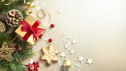 Christmas light gold background with beautiful Golden gift box with red ribbon, fir branches, cones, stars, Christmas cookies, top view, selective focus, copy space.