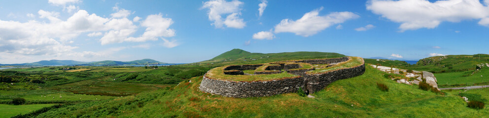 Ring fort in Ireland, panorama with green grass and blue sky