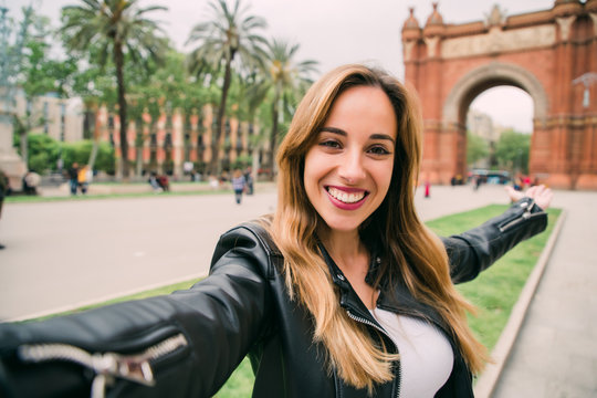Get ready to exciting weekend at Barcelona. Smiling young woman tourist taking selfie on street