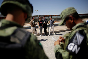 An agent of the National Immigration Institute (INM) talks to Cubans after detained by the Mexican National Guard as they were trying to cross illegally the border between the U.S. and Mexico, in Ciudad Juarez